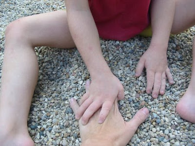 Photo of Joy's hands pulling JoyMama's hand into the gravel