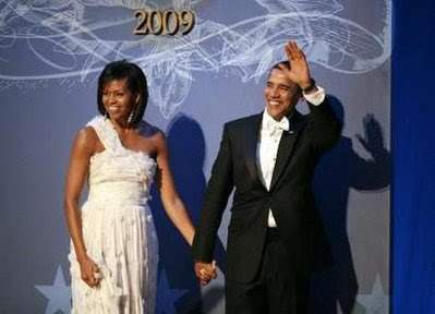 U.S. President Barack Obama waves as he stands with first lady Michelle Obama.