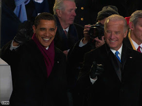 President Barack Obama and Vice President Joe Biden watch the inaugural parade outside the White House.
