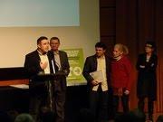 Carles Palau, recogiendo el premio. Al fondo, Samuel Sebatián con el premio en sus manos