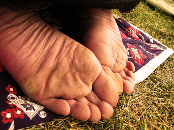 A happy festival goer sitting on his knees and exposing some grass stained, dirty feet at the Telluride Bluegrass Festival.