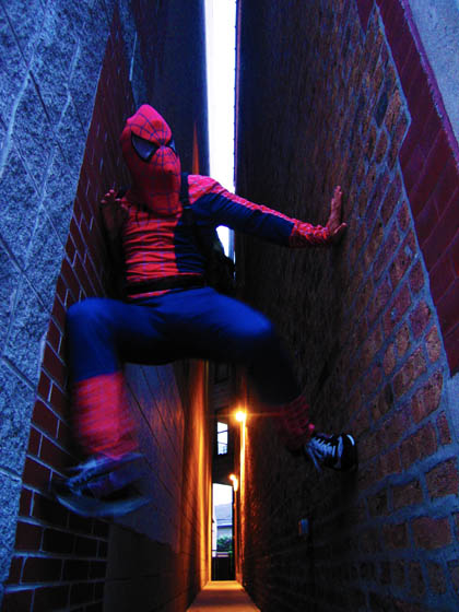 A guy in a loose fitting Spiderman costume scaling walls in Chicago.