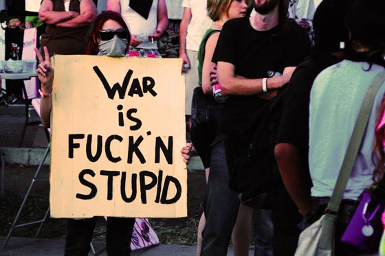 A young war protester with a 'War is Fuck'n Stupid' sign outside the Democratic National Convention in Denver, Colorado.