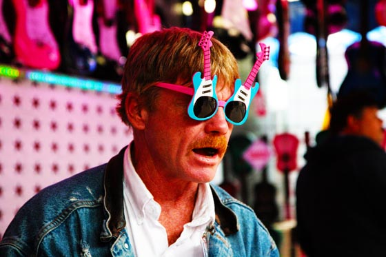 A booth vendor at the Texas State Fair wearing guitar sunglasses and a jean jacket.