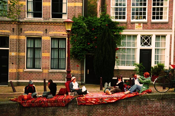 Picnickers lined up on an Amsterdam canal.
