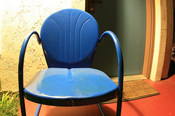 A blue lawn chair outside a hotel room at the Belmont Hotel in the North Oak Cliff neighborhood of Dallas.