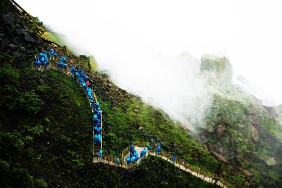 A line of tourists in blue rain gear walking to the bottom of Niagara Falls.