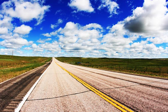 A wide open South Dakota highway under blue sky and big clouds.