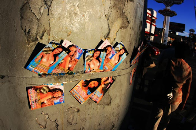 Advertising cards for Las Vegas escorts wedged into a wall on the Vegas strip.