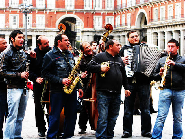 Spanish band of men busking with horns, bass players and an accordion in Plaza Mayor in Madrid, Spain.