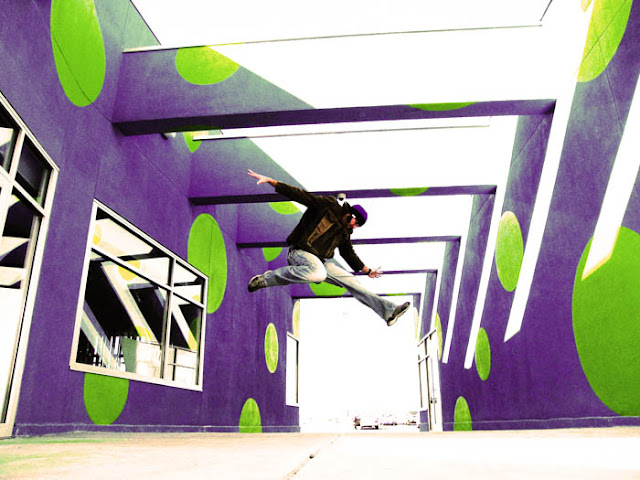 A guy jumping high in a strange purple and green corridor in Lakewood, Colorado.