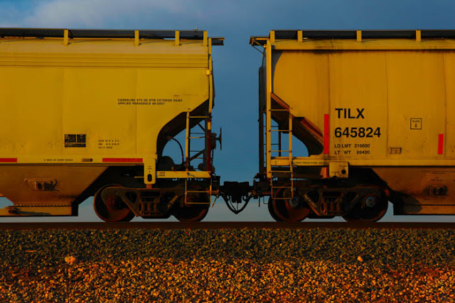 Yellow train cars on a long train traveling on the west Texas railroad.