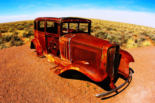 A rusted, antique car placed just off the highway as a monument to The Mother Road, Route 66.  This monument is located just north of Petrified Forest National Park.