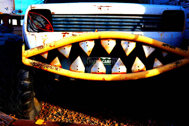 A car with sharp teeth and a happy camper bumper sticker at the Swetsville Zoo in Fort Collins.