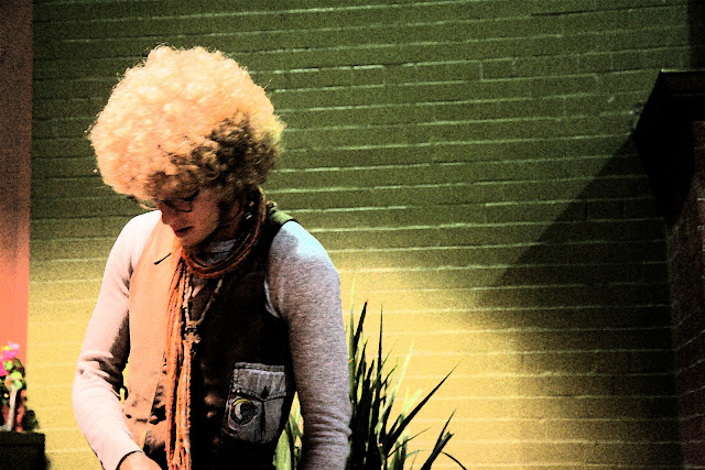 An awesome blonde afro on the head of a very kind, busking, hippie on the street in San Francisco.