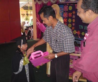 En Shabri Menyampaikan Hadiah Kepada Murid