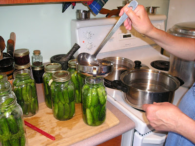 Ladling brine into jars to make dill pickles