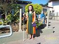 A Perla com o vestido do nosso uniforme em frente ao jardim.