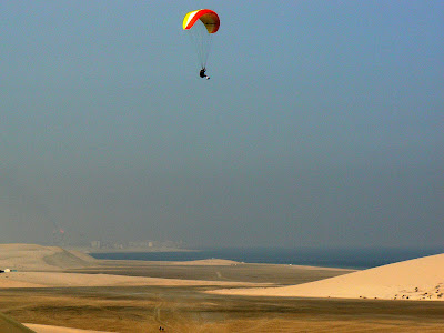 A paraglider hangs high above the desert