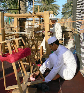 Men work at a loom in Doha's heritage village