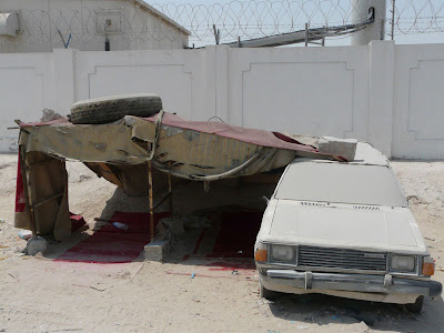 A shelter built out from the side of a wrecked car.