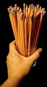 a hand holding a jar full of pencils