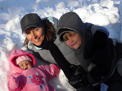 Woman with two children laying in snow pile