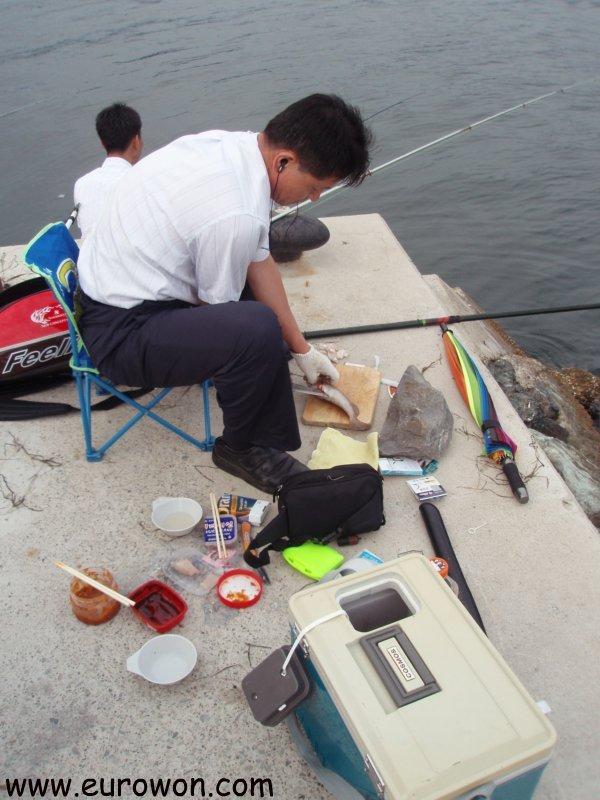 Coreano comiendo sashimi de los peces que va pescando