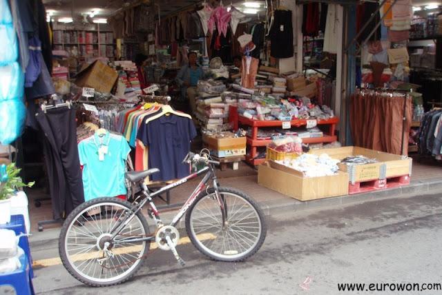 Tienda coreana con una bicicleta delante para que no aparquen lo coches