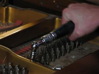 Carefully turning the tuning hammer