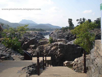 landscape of rocks and rivers and steps going down to the basket boat journey starting point in hogenekkal,polished river side rocks,steps to river bank,south indian tour trips,hogenekkal