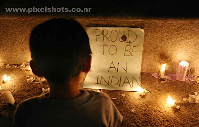 child praying with candles around him and a note saying proud to be an indian,photograph from the community candle prayers taken by professional media photographers
