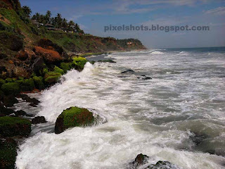 rocks in kerala beaches,sedimentary beach rocks in varkala-trivandrum-kerala-india,indian beach photos,monsson time rough sea waves hitting the beach rocks