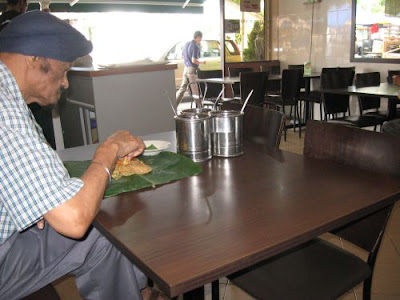 man enjoying his roti canai at Kashmir Cafes