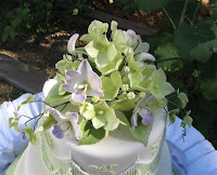 Sugar orchids, hydrangeas, and ivy wedding cake topper