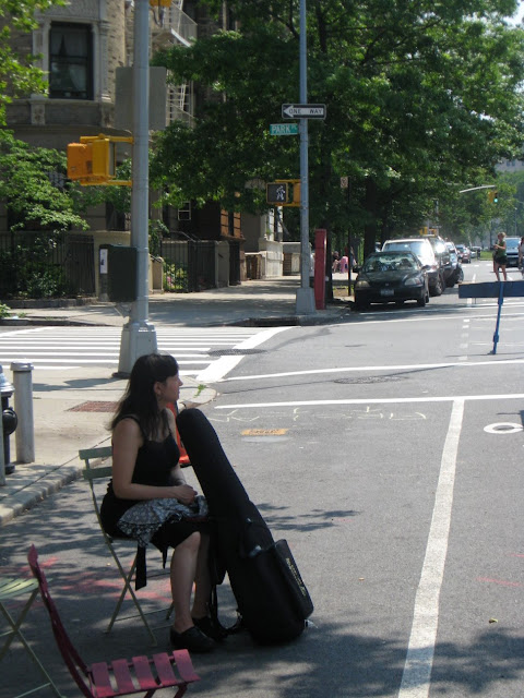 woman sitting alone on street with instrument