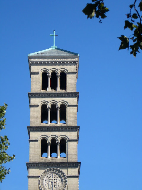 Church tower against the sky with leaves