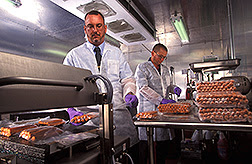 Molecular biologist Chris Sommers (left) and microbiologist Glenn Boyd vacuum-seal hotdogs to get them ready for irradiation. Photo by Stephen Ausmus.