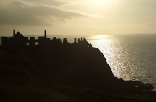 The ruins of Dunluce Castle stand guard over the sea near Portrush at sunset