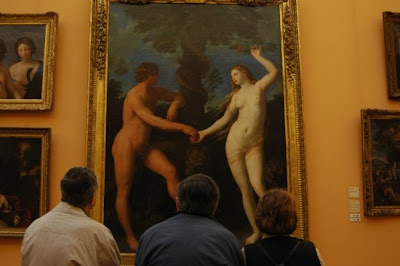 people on bench looking at naked art in italy musuem