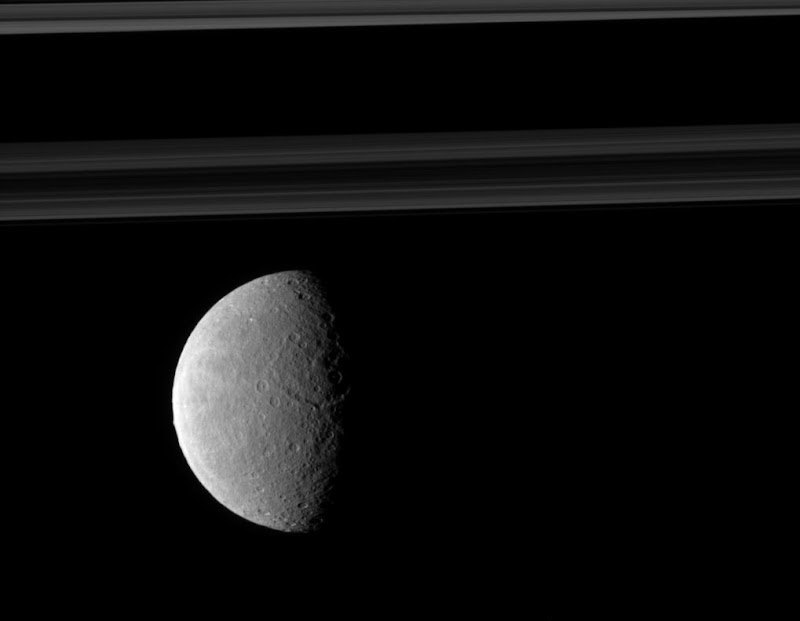 Rhea's trailing hemisphere shows off its wispy terrain on the left of this image which includes Saturn's rings in the distance.