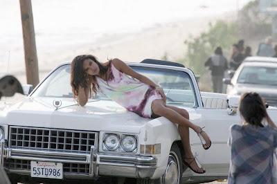 Freida Pinto psosando encima de una carro