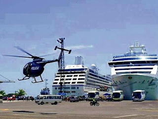 A police helicopter flies over the port of Limon as cruise tourists disembark. (Photo: Mario Carvajal/La Nacion)