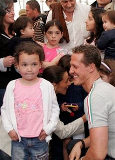 Former Formula One champion Michael Schumacher smiles at Nidalin Mendoza, 5, during his visit to shelter for people left homeless by Thursday's 6.1-magnitude earthquake in Poasito de Vara Blanca, Costa Rica, Wednesday, Jan. 14, 2009. (AP Photo/Kent Gilbert)