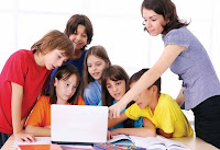 Photo:  A group of children with their teacher around a single laptop