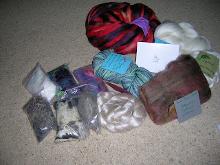 photo of secret pal package containing variety of fibres, including pecil roving, silk and bison down containing