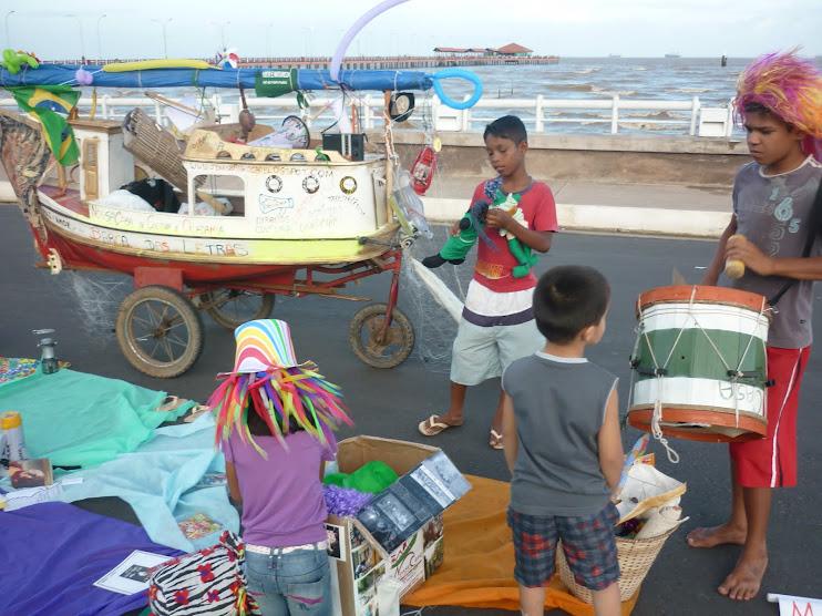 Crianças e adolescentes (vítimas do trabalho infantil) brincando de ler em frente ao Rio Amazonas