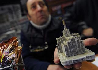 Na foto, vendedor mostra réplica do Duomo (catedral de Milão) em loja no centro de Milão nesta segunda-feira (14). Ela é semelhante à que teria atingido o premiê italiano.
