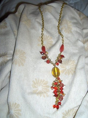 Colar elaborado em corrente dourada, e contas em vidro douradas e vermelhas.
