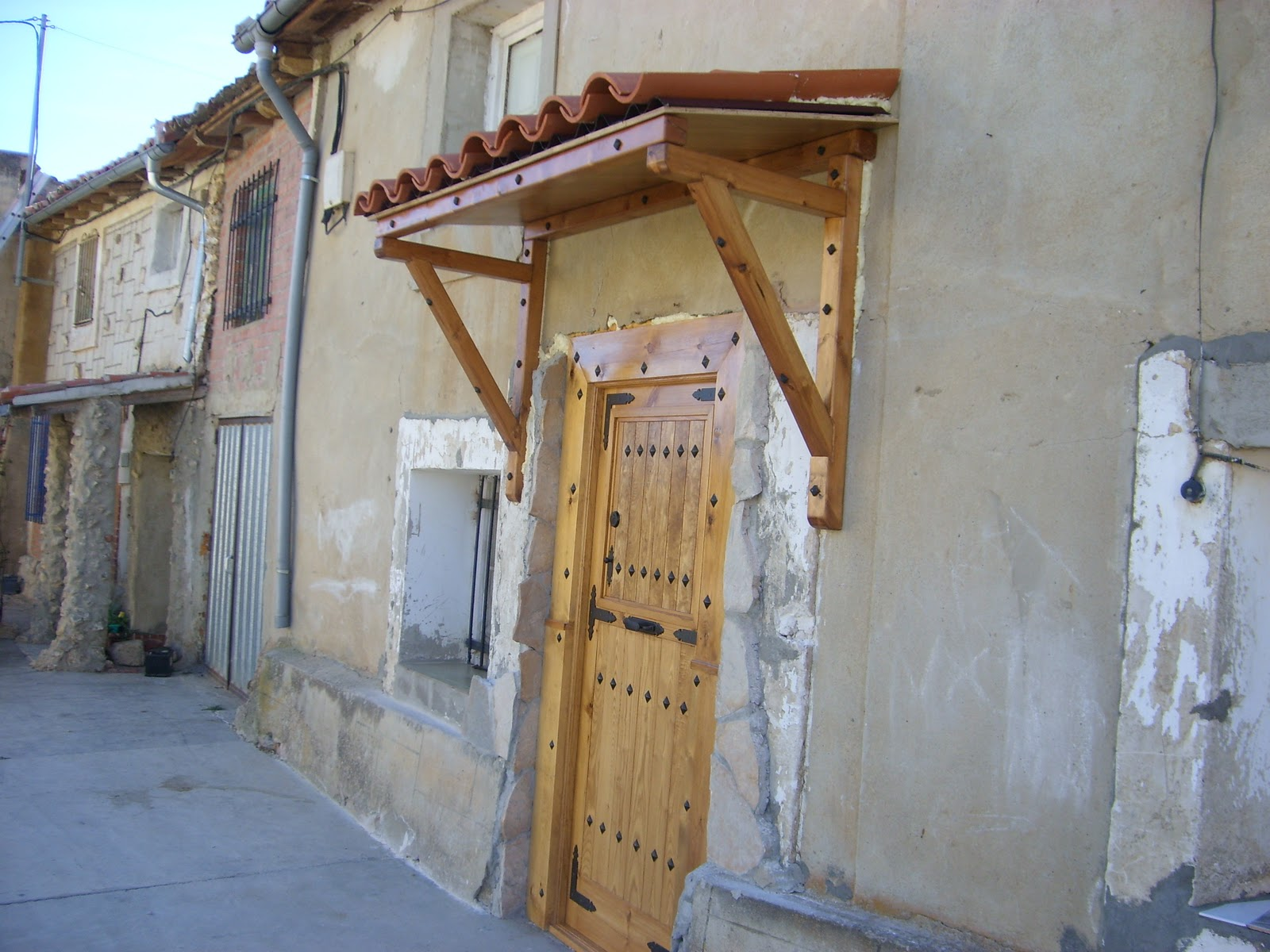 Modifica tu casa tejado sobre puerta de entrada for Tejado madera onduline